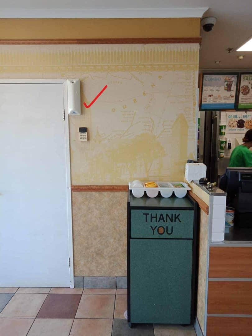 Fly Lady automatic dispenser wall mounted beside Subway rubbish bin