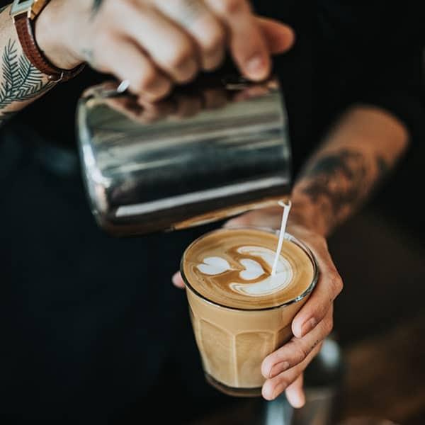 Barrista adding milk to a latte